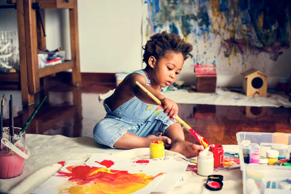 A little boy on a work table making a painting.