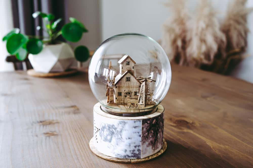 This is a big homemade snowglobe on a wooden table.