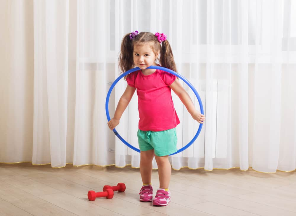 A little girl playing with a hula hoop.