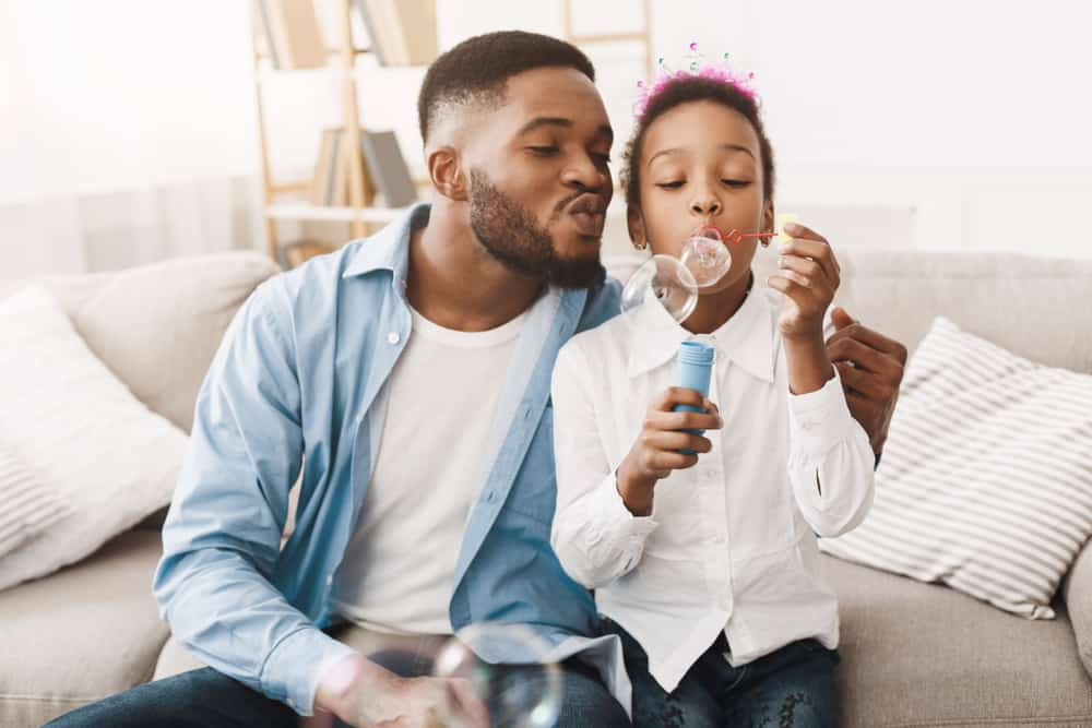 A father and daughter playing with bubbles in living room.
