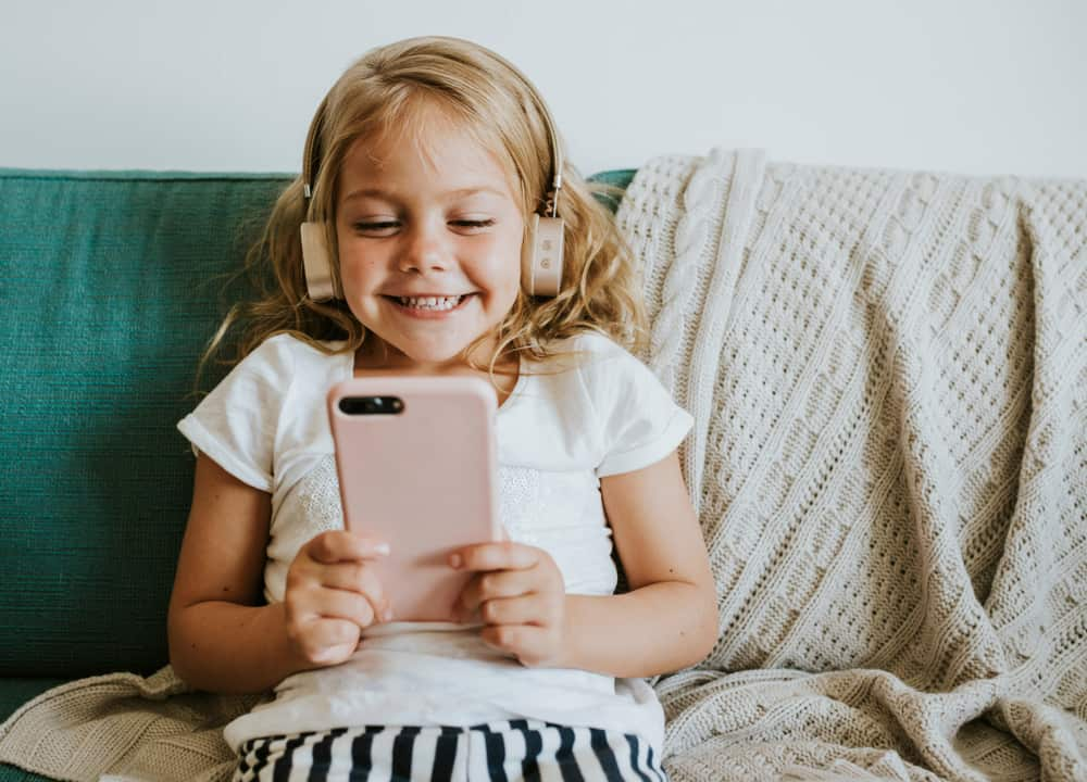 A girl playing on a smart phone in the living room.