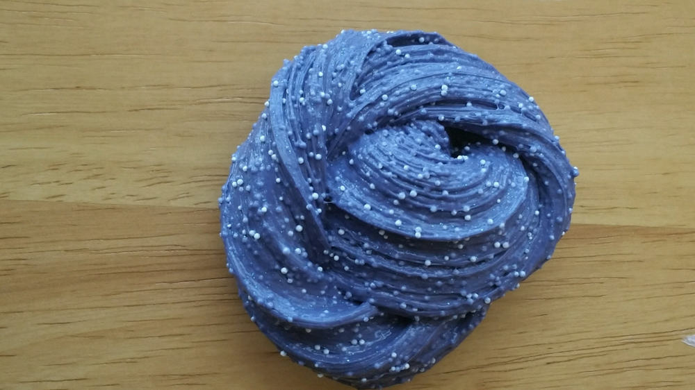 This is a dark blue microfloam slime on a wooden table.