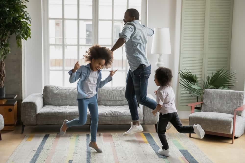 A family dancing in the living room.