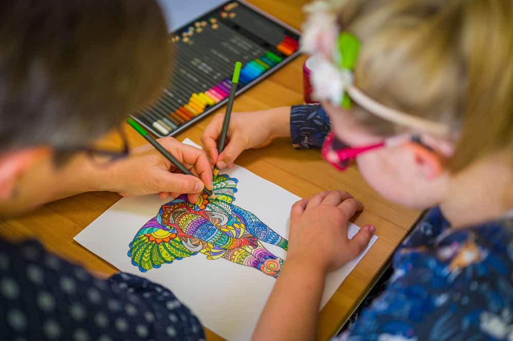 A couple of kids coloring in an elephant illustration.