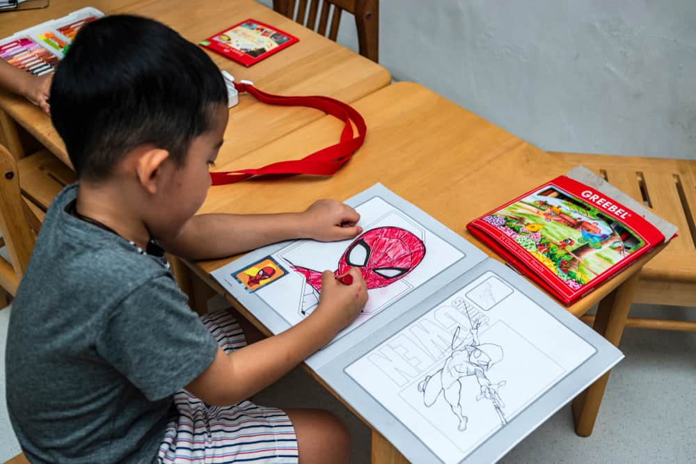 A kid coloring in a Spiderman coloring book.