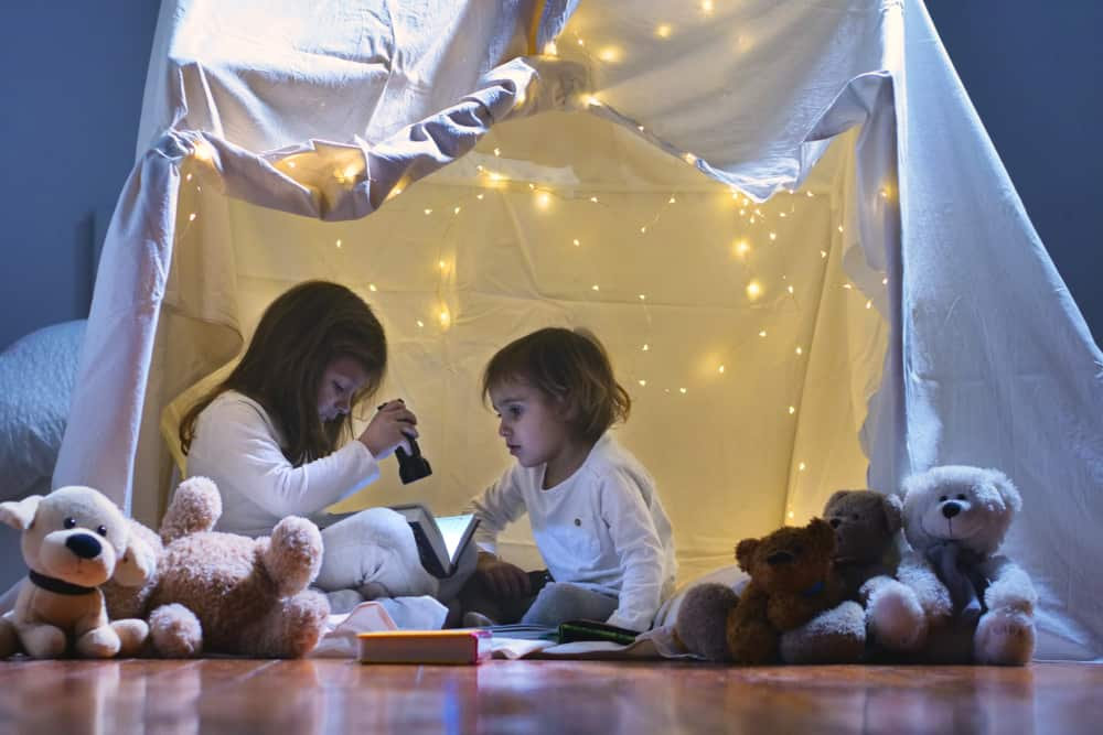 A couple of kids reading in a blanket fort with Christmas lights.