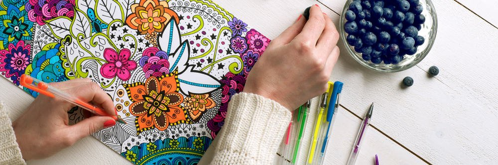 A woman coloring in the detailed adult coloring book.