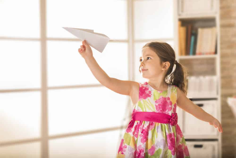 This is a close look at a kid playing with a paper airplane.