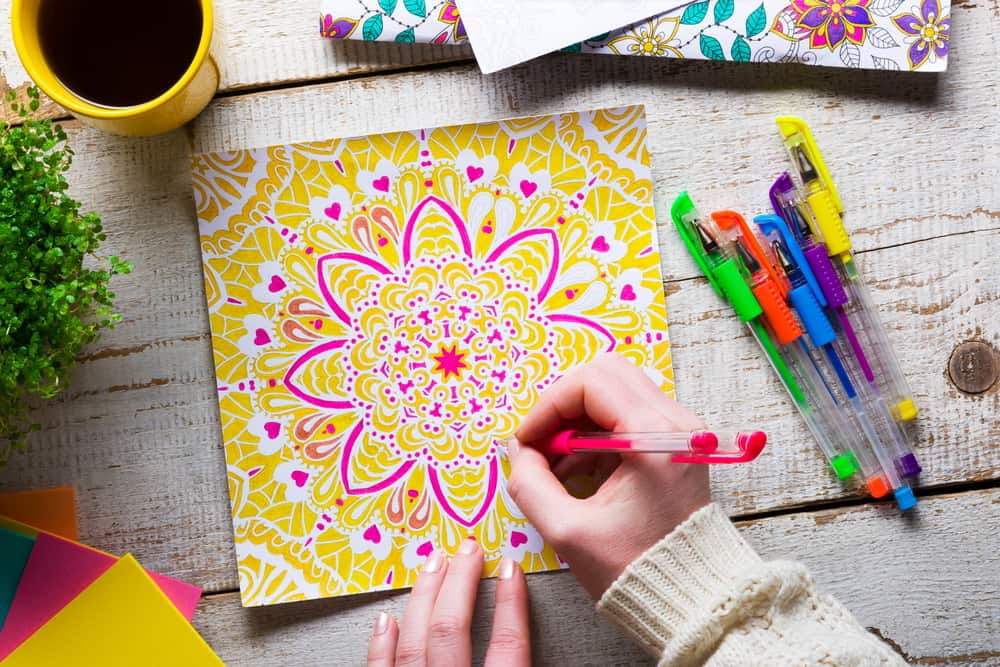 A woman coloring in the detailed patterns with colorful pens.