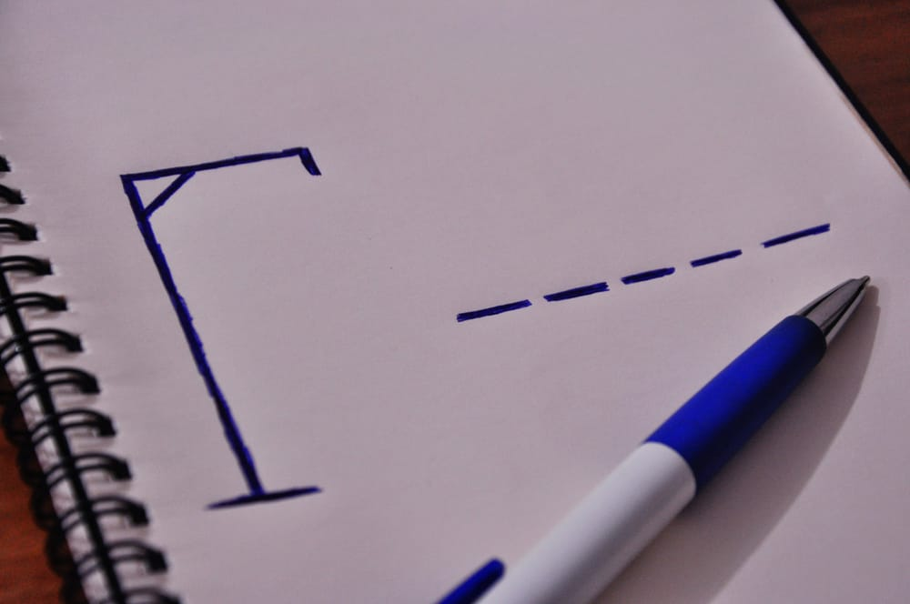 This is a close look at a hangman game on notebook with a pen.
