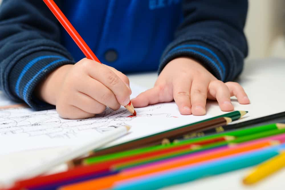 A close look at a kid coloring in the coloring book with color pencils.
