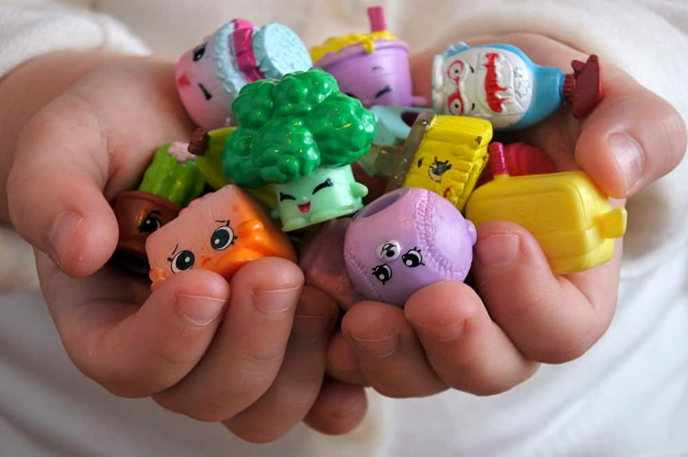 A close look at a hand full of collectible shopkins toys.