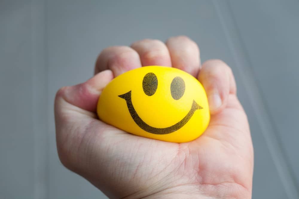 A yellow stress ball with a smiley face on it being squeezed.