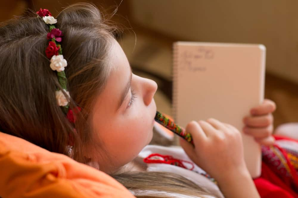 A close look at a girl writing on her journal.