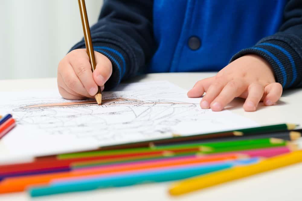 A close look at a kid using a brown color pencil.