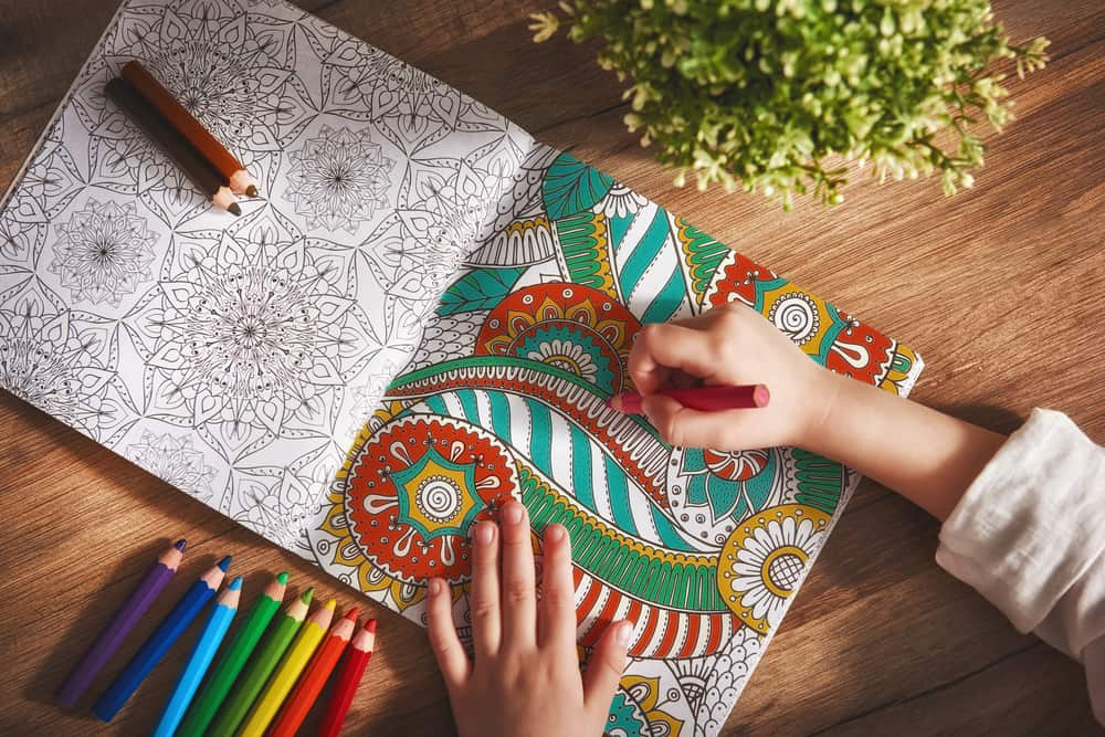 A child coloring in an adult detailed coloring book.