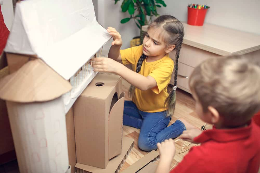 These are a couple of kids making a cardboard castle.