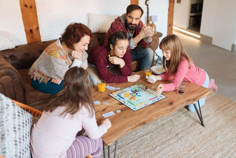 This is a family playing a board game in the living room.