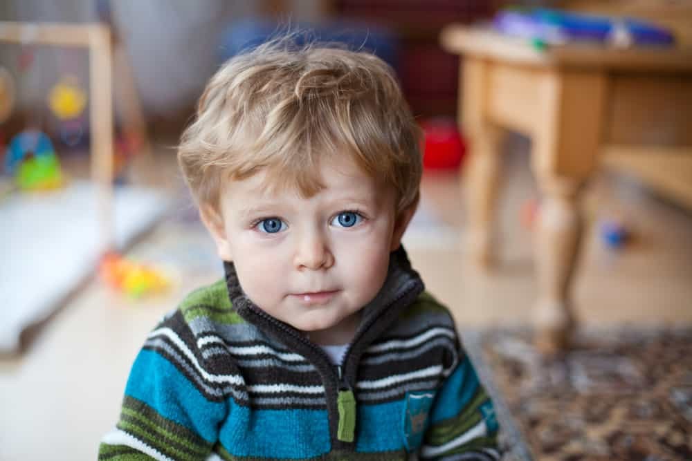 This is a blond two-year-old boy wearing a blue striped sweater.