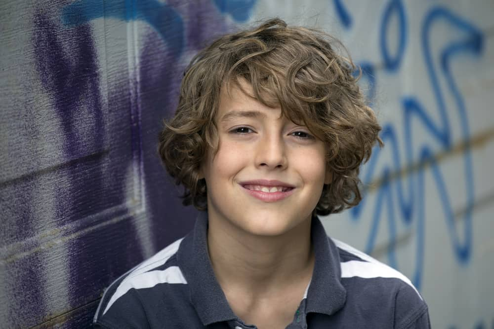 A smiling brown-haired 11-year-old boy wearing a gray shirt.