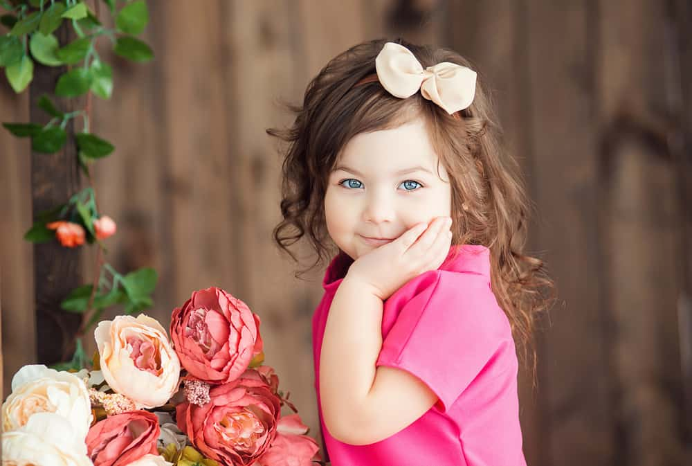 This is a three-year-old girl wearing a bow playing with flowers.