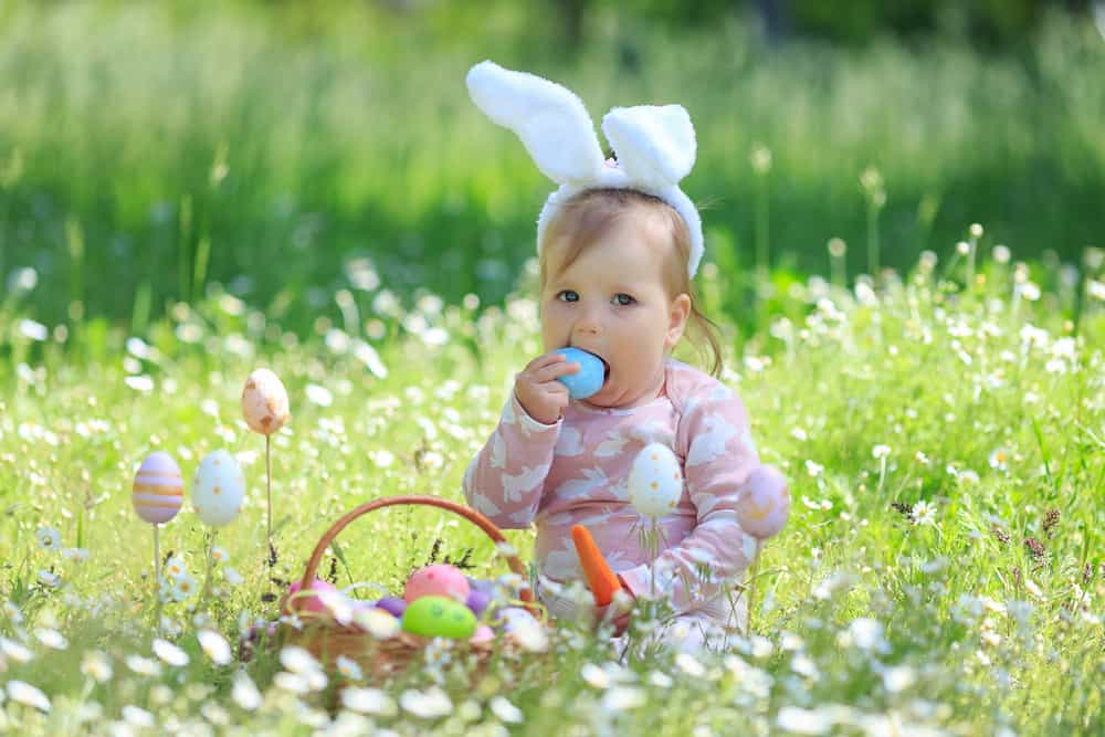 This is a one-year-old girl wearing bunny ears while playing with Easter eggs.