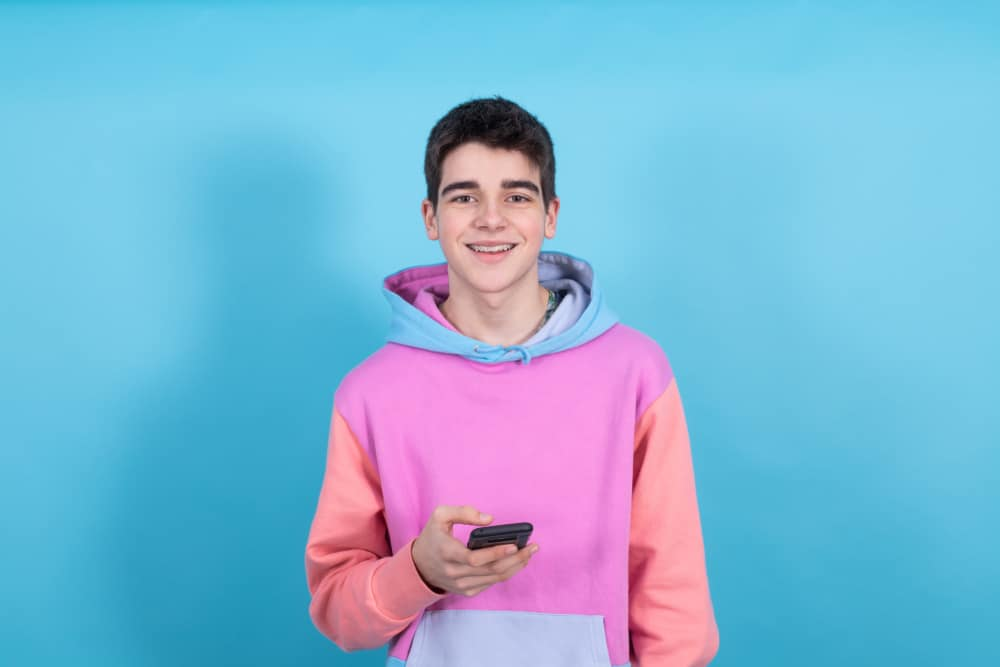 This is a thirteen-year-old boy wearing a colorful hoodie and holding his phone.