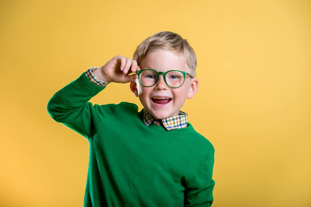This is a three-year-old boy wearing a green sweater and a green pair of glasses.