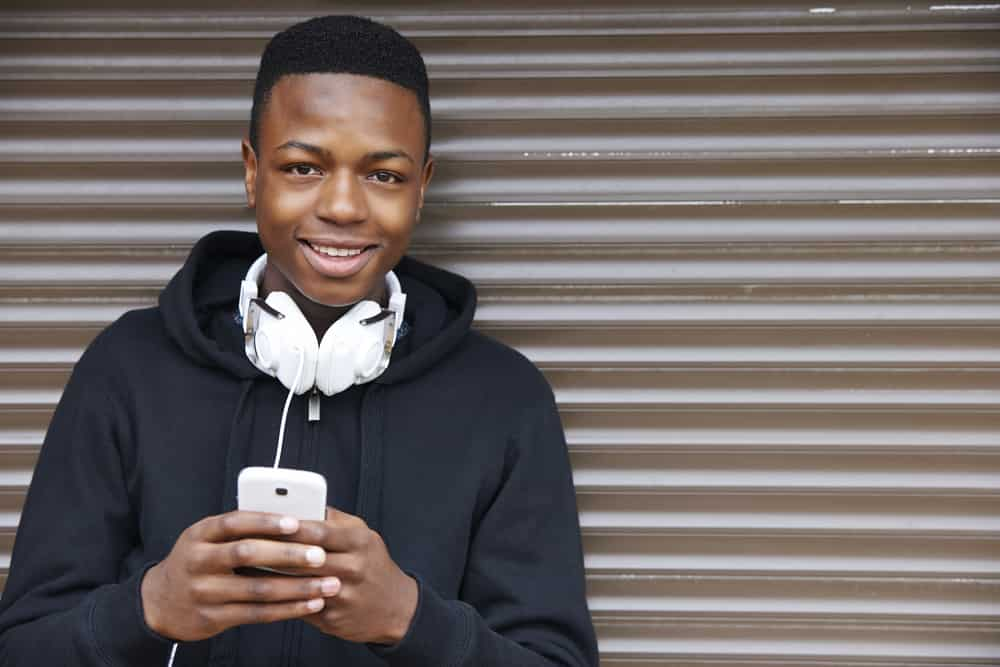 This is a 12-year-old boy wearing a black hoodie with a white headphone and smartphone.
