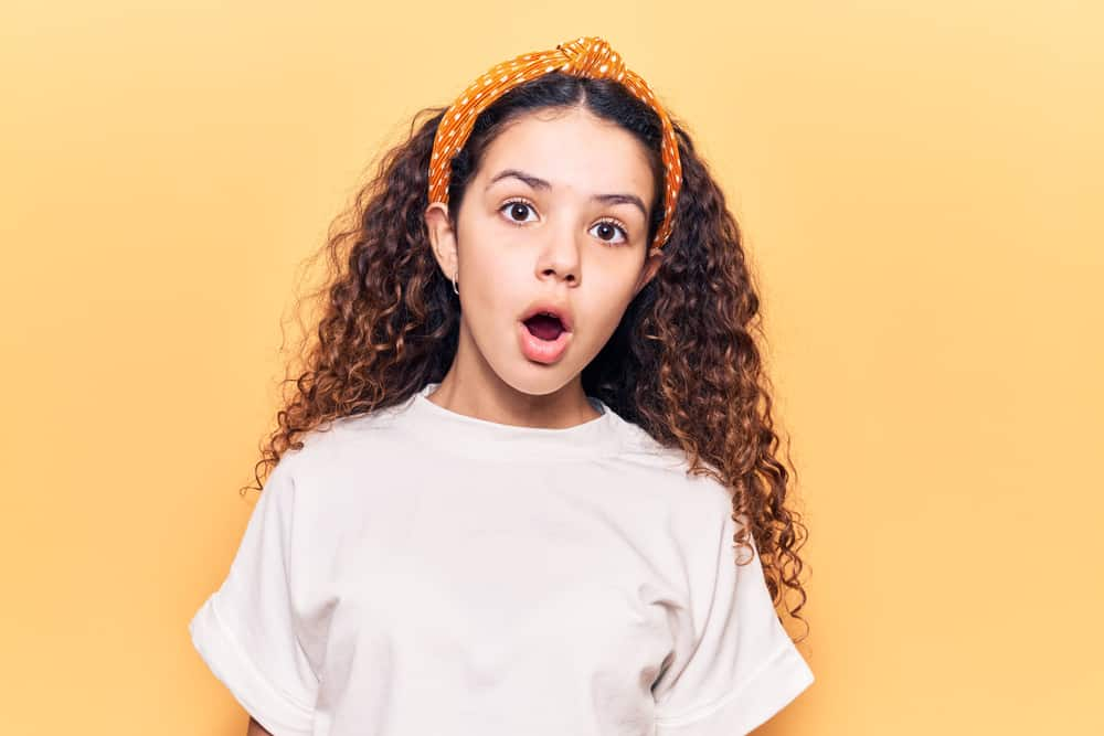 A little girl with curly, long hair wearing a dotted headband and white shirt poses with surprised expression against the yellow wall.