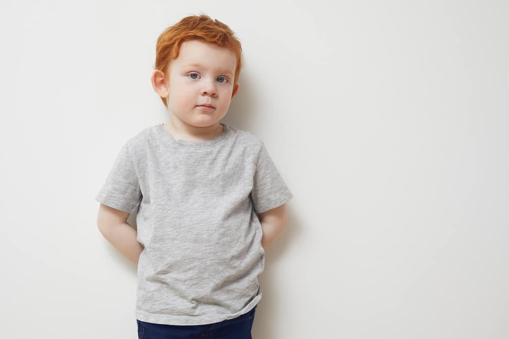 Portrait of a redhead boy standing against the white wall.