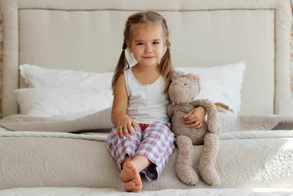 Little girl in a plaid pajama hugging her stuffed toy while sitting on the edge of the bed.
