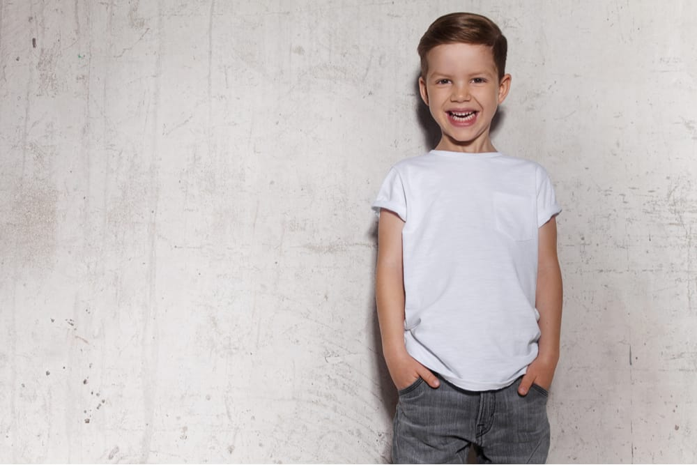 Little boy in white shirt posing against the grunge concrete wall.