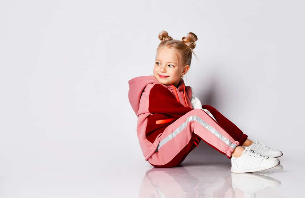 Little girl in pink tracksuit and pigtail buns sitting on the floor.