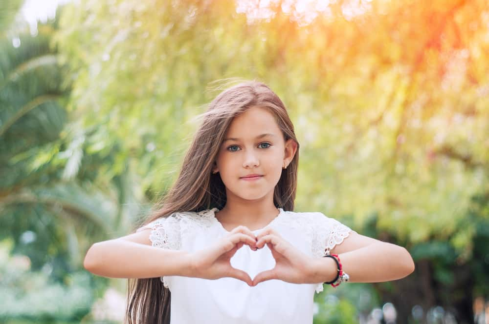 A little girl in the park with long hair creating heart shape with her hands.