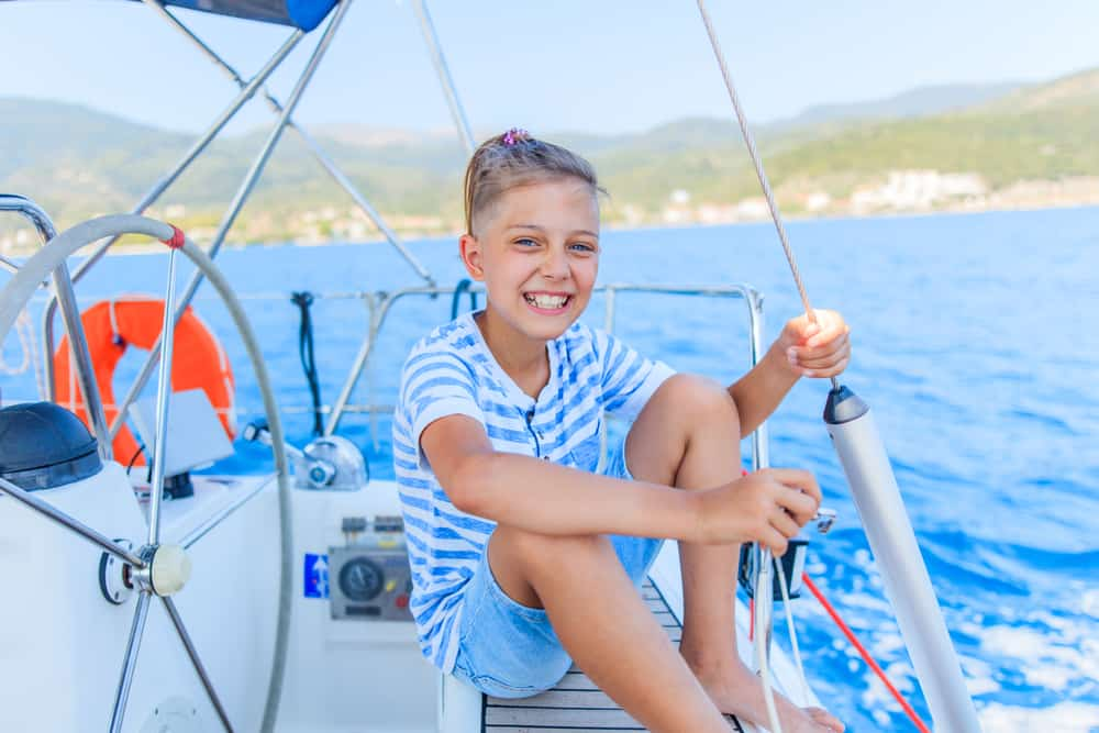 Boy sitting on a yacht while sailing on a summer cruise.