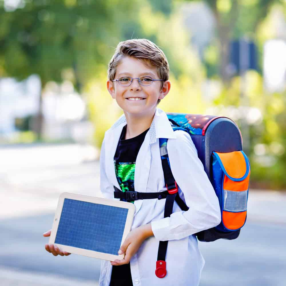 Little boy with eyeglasses and backpack holding a chalk desk on his way to school.