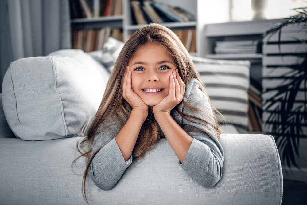 Little girl with long, blonde hair comfortably lying on the couch.