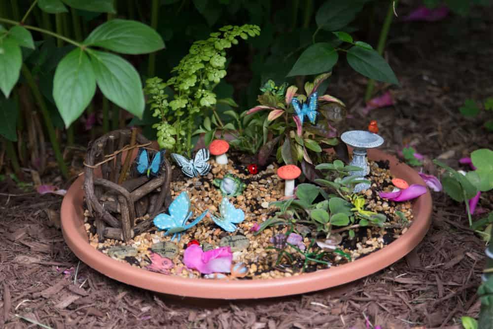 DIY fairy garden in plant saucer filled with butterflies, bird bath, mushrooms, and a driftwood bench.