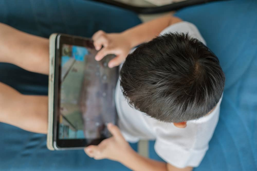 Little boy sitting on a couch playing games on a tablet.