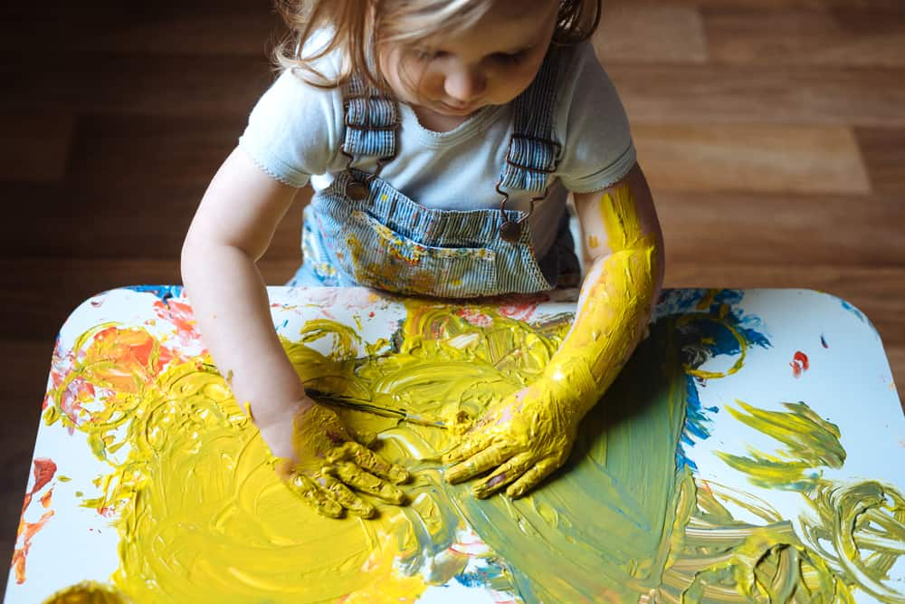 A girl painting with her hands on the table using yellow paint.