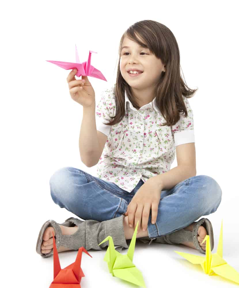 Girl on a cross sitting position holding an origami bird.