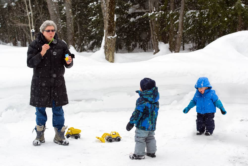 Grandmother blows bubbles for two little boys outside the snow.