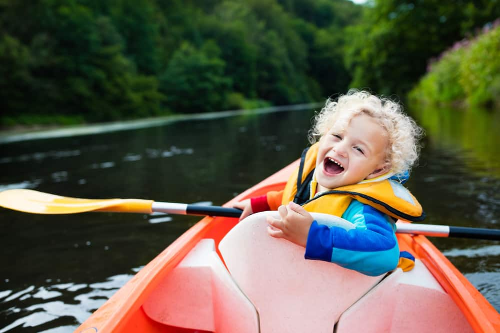 Little boy kayaking on a river during a summer day.