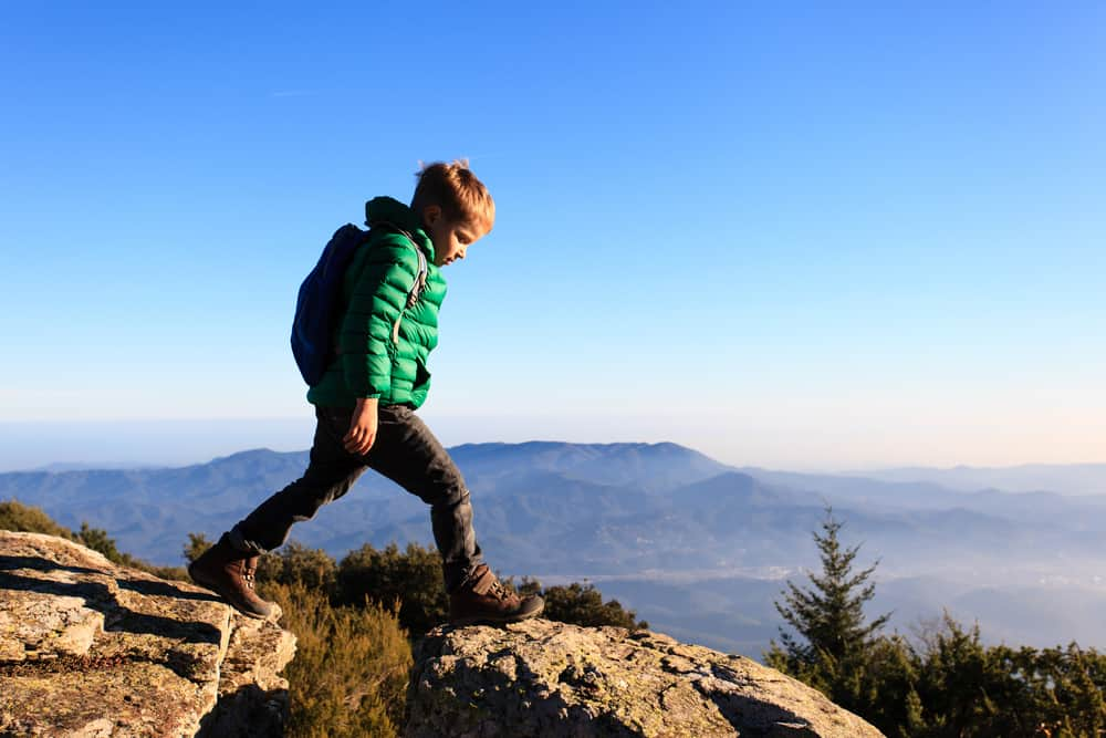 Little boy wearing green winter jacket and backpack hiking along scenic mountains.