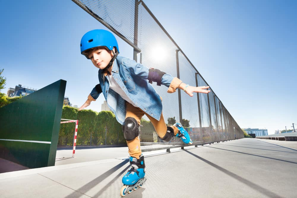 Little boy equipped with head gear and pads doing tricks at skate park.