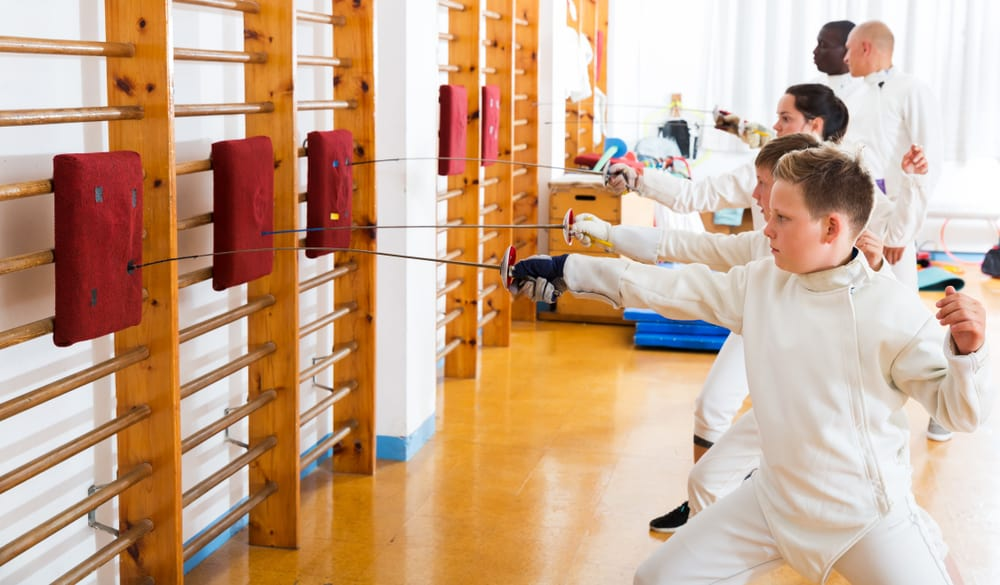 Kids along with adults practicing techniques of fencing in training room.