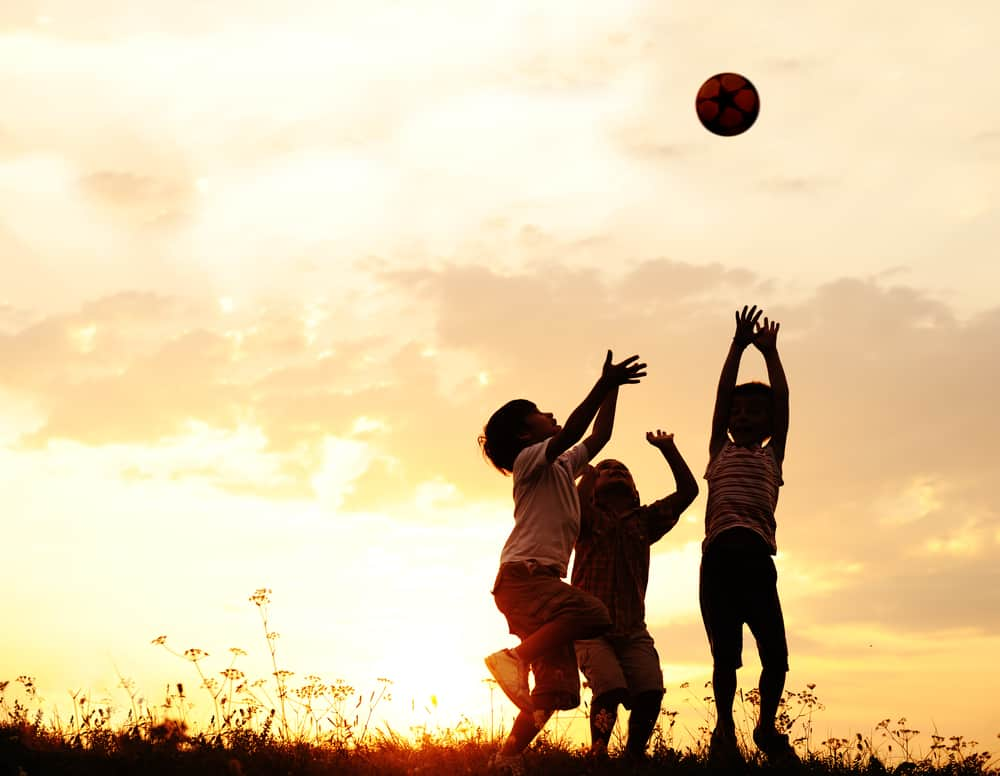 Group of kids playing with ball during sunset.
