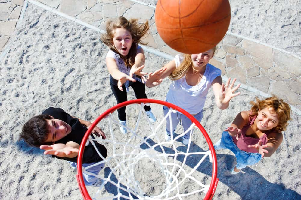 A group of teens playing basketball in the park.
