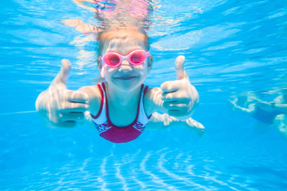 Little girl wearing pink goggles and swimsuit deftly swim underwater in pool.